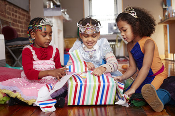 Girls with tiaras opening gift at party