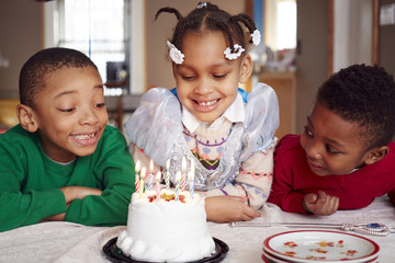 Smiling children admiring cake at party