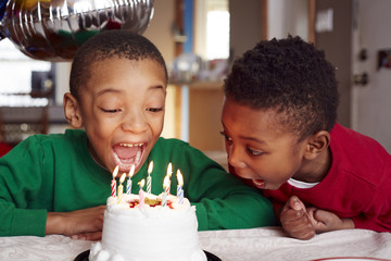 Boys blowing out birthday cake candles at party