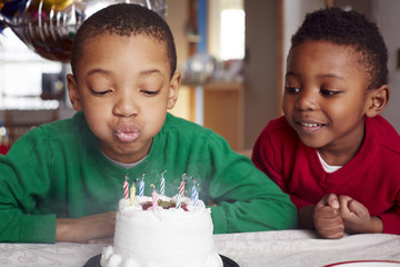 Black boy blowing out cake candles at party