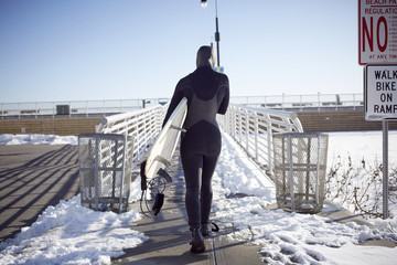 Black teenage girl in wetsuit carrying surfboard in winter