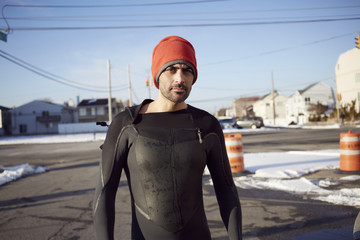Black man in wetsuit standing in snow