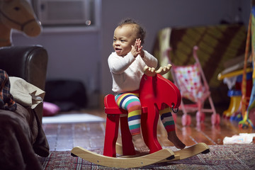 Mixed race baby girl playing on rocking horse