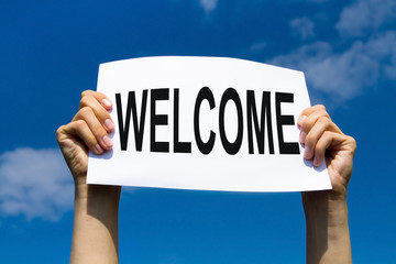 welcome concept, hands holding paper sign on blue sky