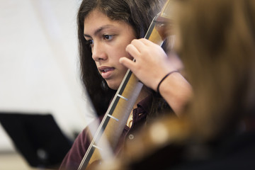 Pacific Islander student rehearsing cello in high school band class