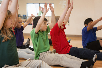 Children stretching arms in gym class