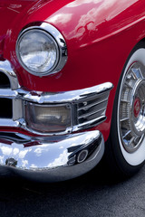 Closeup of a front classic red roaster car finder and headlight