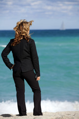Business Metaphor: Working Vacation Beautiful business standing on the beach looking at the ocean. Sailboat in far background.