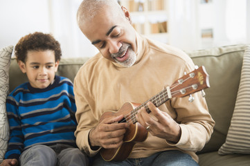 Mixed race grandfather and grandson playing ukulele