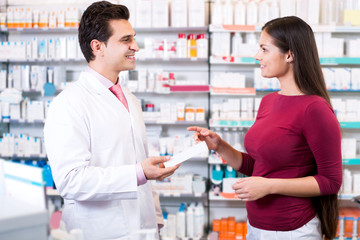 Experienced pharmacist counseling female customer