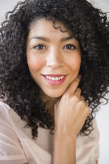 Mixed race woman with curly hair smiling