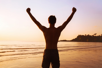 sport background, silhouette of strong sportive man on the beach, winner or achievement concept