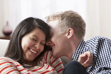 Smiling couple playing on sofa