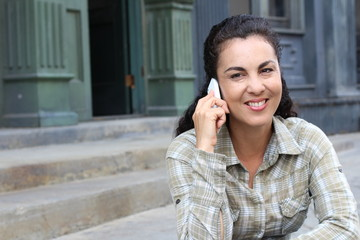 Middle-aged happy excited laughing woman talking on mobile phone isolated outdoors city urban background.