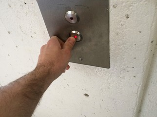 Hand pressing down button on elevator call panel