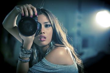 Glamorous woman photographer holding camera