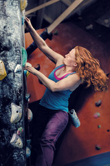 Redhead Woman Indoor Rock Climbing Toward Light. Strong Woman Climbing Wall