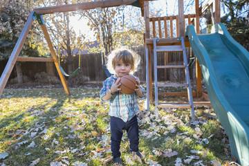 Caucasian boy holding basketball in backyard