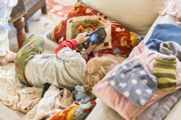 Caucasian boy using cell phone on sofa