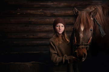 Caucasian girl standing with horse in barn