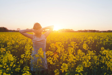 young woman enjoying summer and nature in yellow flower field at sunset, harmony and healthy lifestyle