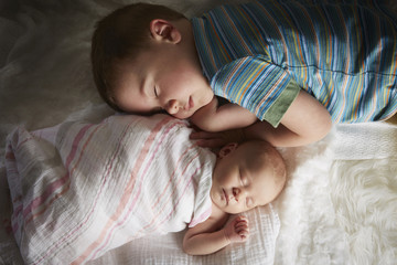 Boy napping with newborn sibling on bed