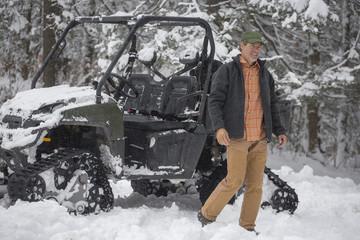 Mixed race man walking near snow vehicle in snow
