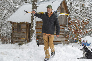 Mixed race man carrying skis near snowy shed