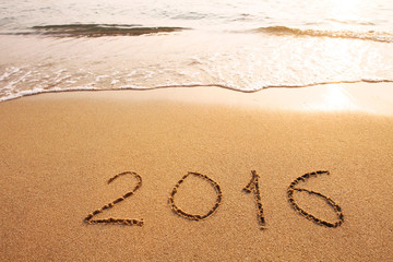 new year 2016 concept, text written on the sand of beach