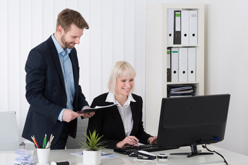 Two Young Businesspeople Working On Computer