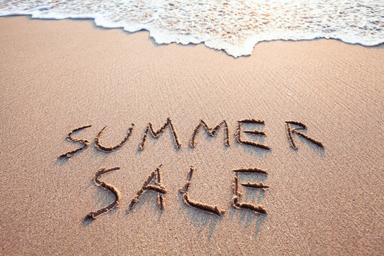 summer sale sign on the beach, text written on the sand