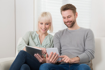 Young Couple Holding Digital Tablets