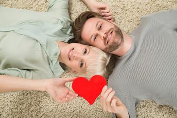 Couple Lying On Carpet Holding Heart