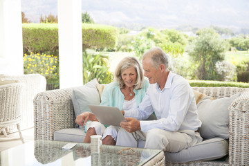 Caucasian couple using digital tablet on sofa outdoors