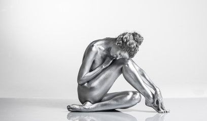 Nude Caucasian woman with silver body paint sitting
