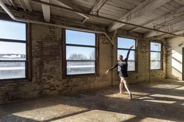 Caucasian ballet dancer performing in sunny loft