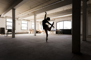 Caucasian ballet dancer performing in loft room
