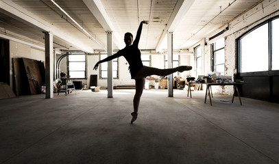 Caucasian ballet dancer performing in loft