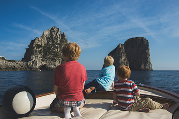 Caucasian brothers on boat admiring rock formations in ocean, Isle of Capri, Naples, Italy