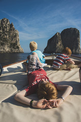 Caucasian brothers on boat admiring rock formations and ocean, Isle of Capri, Naples, Italy