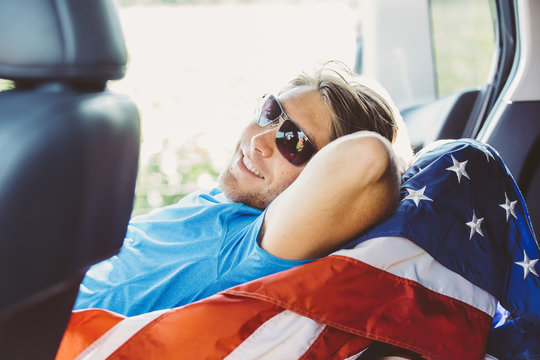 Smiling man lying on American Flag in car