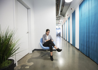 Indian businesswoman using cell phone in office hallway
