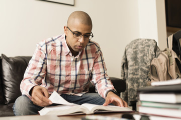 Mixed race soldier reading book on living room sofa