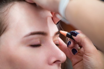 Cosmetologist applying permanent make up (tattoo) on eyebrows.
