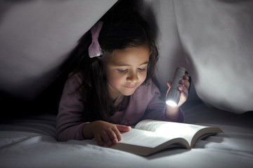 Little Girl Reading a Book in Bed and Using a Small Lantern