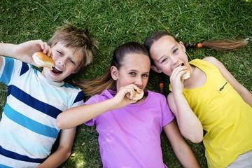 Portrait of children eating bun