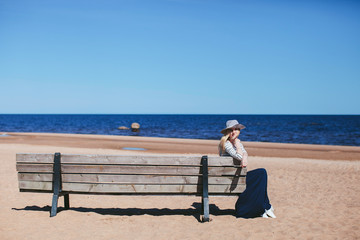girl sitting on a bench on the beach