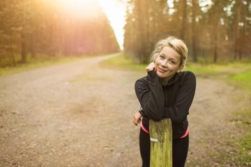 Blonde Frau auf Schotterweg in der Sonne stützt auf einem Holzpfeiler