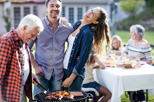 Couple and a senior man at barbecue grill preparing a barbecue