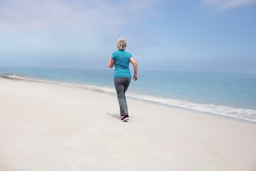Rear view of senior woman jogging on the beach